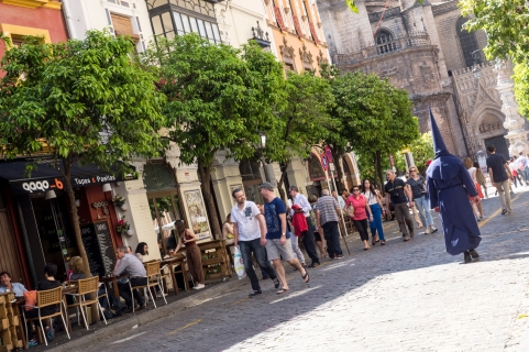 A lone penitent wanders the streets of Seville.